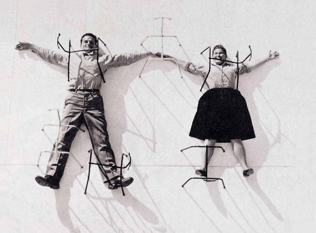 "Charles und Ray Eames with various bases for their famous ""Plastic Chair"""